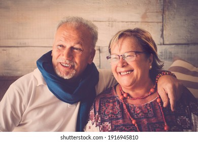 Happy old mature couple have fun at home in smiling portrait - elderly lifestyle man and woman sitting together on the sofa laughing and enjoying with love - retirement indoor leisure activity