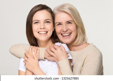 Happy old mother embracing young daughter looking at camera, smiling senior middle aged mom hug teen girl, different generation women family isolated on grey white studio background headshot portrait