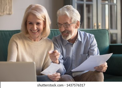 Happy old retired couple paying domestic bills online using computer app, satisfied bank clients senior middle aged grandparents holding papers make loan insurance payment at home on laptop on sofa