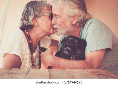 Happy old senior couple people in love kiss eachother and hug their lovely black dog pug - home leisure activity and forever together concept family and relationship