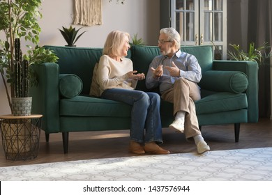 Happy old senior couple talking laughing sit on sofa together, honest elder mature family husband and wife chatting bonding having fun spending time joking relaxing in modern living room at home