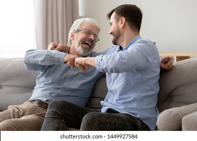 Happy old senior father and son fists bumping, celebrating success or greeting each other, mature aged dad and millennial man having fun together, sitting on couch at home, enjoying weekend