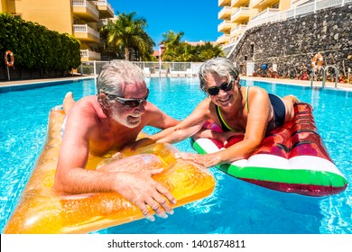 Happy old senior people couple enjoy the summer and have fun with coloured lilos together inthe wimming pool - Cheerful man and woman mature caucasian in joy under the sun