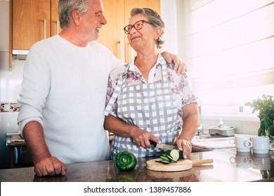 Happy old senior retired beautiful white hair couple of people cooking together at home in the kitchen cutting vegetables for healthy food lifestyle concept