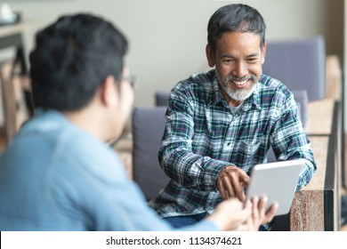 Happy old short beard asian man sitting, smiling and listen to partner that showing presentation on smart digital tablet. Mature man with social media technology teaching or urban lifestyle concept.