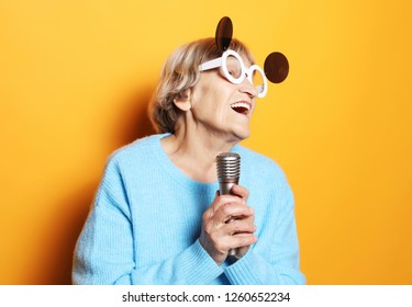 happy old woman with big eyeglasses holding a microphone and singing isolated on yellow background, close up