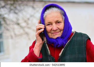 Happy old woman with cell phone in village