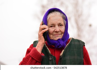 Happy old woman with cell in village