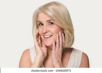 Happy old woman love touching her skin on face. Delighted elderly female enjoy herself, reflection in mirror, looking at camera. Studio headshot isolated on gray background. Skin care, cosmetology