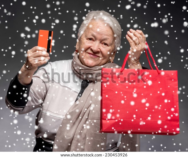 Happy old woman with shopping bags and credit card. Christmas and holidays concept