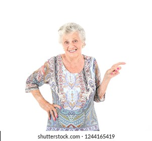 Happy old woman smiling while pointing her finger to one side against a white background