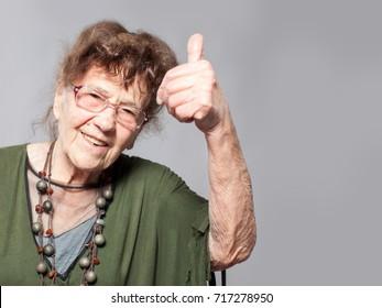 Happy old woman. Stylish elderly woman. Studio shot.