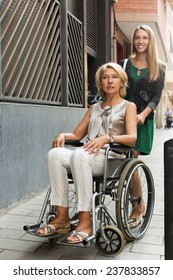 Happy old woman in wheelchair with female assistant outdoor