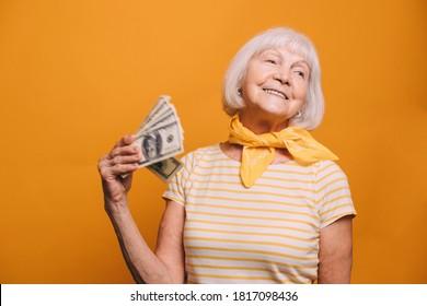 Fröhliche alte Frau mit weißem Haar und grauen Augen mit gelbem Kravat und hellem T-Shirt, Blick seitlich und winkt ein Fan von unscharfem Geld. Frau einzeln auf orangefarbenem Hintergrund