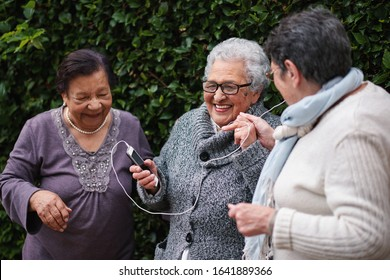 Happy old women listening to music on smartphone wearing earphones smiling enjoying fun celebrating retirement together outdoors