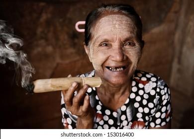 Happy old wrinkled Asian woman smoking traditional tobacco. Bagan, Myanmar.