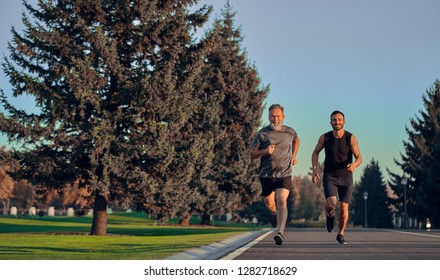The happy old and young sportsmen running on the road