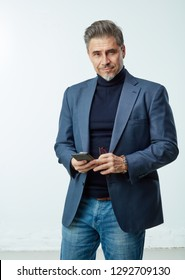 Happy older businessman with gray hair in business casual using smart phone, smiling.