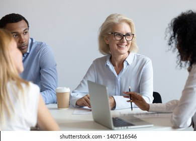 Happy older commercial client representative discussing deal with african young partner at group negotiation, diverse business people workers sitting at office table talking at team corporate meeting