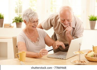 Happy older couple doing online shopping, laughing wife pointing at screen of laptop computer.?