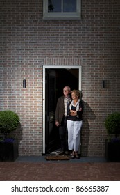 Happy older couple in front of a house