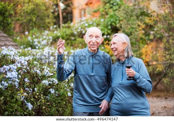 Happy older couple in matching outfits talking about something outside