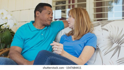 Happy older couple talking on the front porch of their house. Smiling African American and Caucasian husband and wife having conversation outside their home on a sunny day