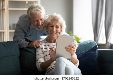 Happy older couple using computer tablet together at home, excited mature man and woman looking at mobile device screen, shopping or chatting online, sitting on cozy couch in living room
