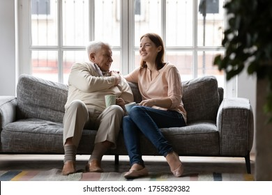 Happy older man and adult daughter drinking tea or coffee together, sitting on cozy couch, smiling young woman and mature father having fun, enjoying leisure time, talking, sharing news