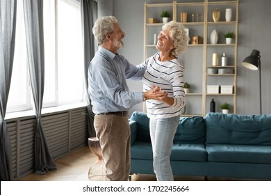 Happy older man and woman dancing to music in cozy living room, senior family celebrating anniversary, smiling mature wife and husband hugging, holding hands, enjoying tender moment