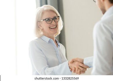 Happy older mature businesswoman shaking hand of male partner boss client greeting getting promoted rewarded, making business deal, respect, trust and gratitude handshake at business meeting concept