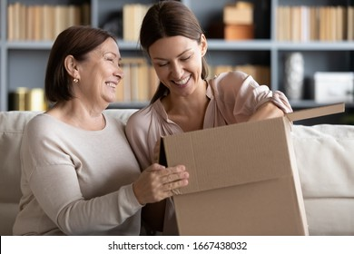 Happy older mature mommy sitting on couch with smiling grownup child, unpacking parcel together at home. Excited different female generations clients unboxing ordered goods from internet store.
