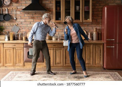 Happy older senior loving family couple having fun in kitchen, singing favorite karaoke songs in utensils. Positive joyful middle aged spouse enjoying funny domestic weekend activity together indoors.