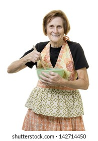 Happy older woman baking stirring up some dough