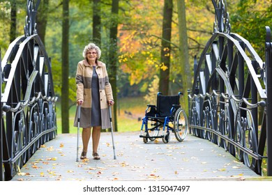 happy older woman practicing walking on crutches in autumnal park with wheelchair in the background