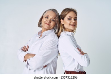 A happy older woman with a short haircut and a young daughter are smiling at the camera and have their arms crossed over their breasts