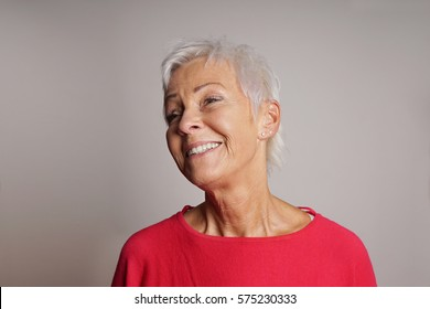 happy older woman with trendy short white hair laughing. gray background with copy space.
