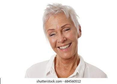 happy older woman with trendy short white hair and toothy smile. isolated on white