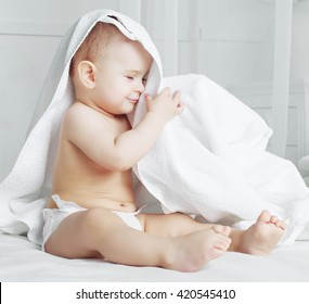 happy one year old baby wearing diapers with a towel in bed at home