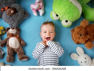 Happy one year old boy lying with many plush toys on blue blanket