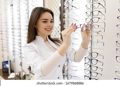 Happy optician standing in optical store, young female optometrist in optics shop looking at eyeglasses. - Shutterstock ID 1679868886