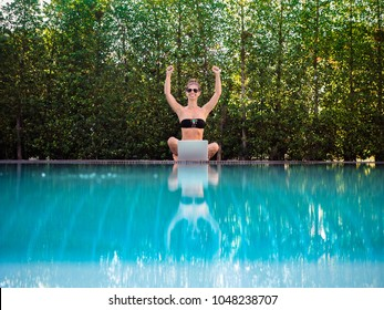 happy, optimistic and cheerful digital Nomad Girl making fists while working with her laptop outdoor at the pool