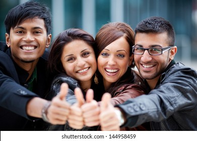 Happy optimistic group of young Asian friends standing with their heads close together laughing and giving a thumbs up gesture