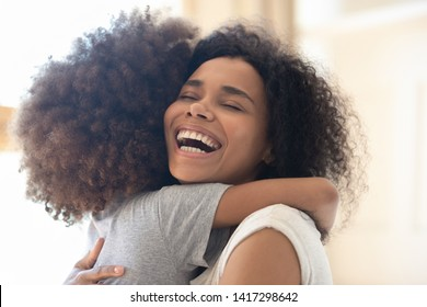 Happy overjoyed african american single mother hugging cute little kid daughter and laughing, cheerful loving black mom embracing child girl having fun playing cuddling bonding feeling joy affection