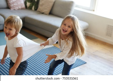 Happy overjoyed female child laughing and screaming with joy, pulling her excited little sister by white t-shirt while playing tag at home or kindergarten, feeling joyful. Kids, leisure and fun