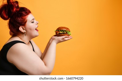 Happy overweight fat woman happy hold burger cheeseburger sandwich with beef in hand on yellow background. Healthy eating diet fast food concept