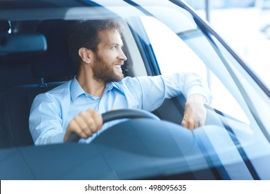 Happy owner. Handsome bearded mature man sitting relaxed in his newly bought car looking out the window smiling joyfully