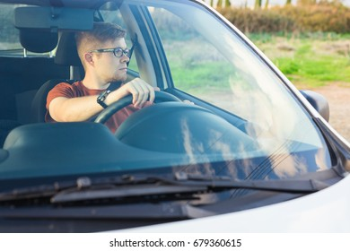 Happy owner. Handsome young man sitting relaxed in his newly bought car looking out the window