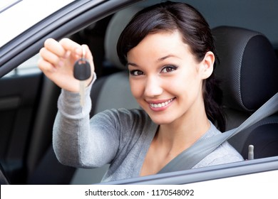 Happy owner of a new car is showing the car key. Pretty girl driver