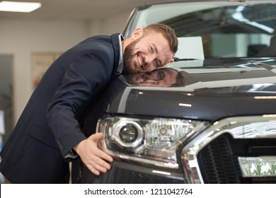 Happy owner of new dark blue automobile posing with vehicle. Handsome man lying on car hood and hugging it. Customer wearing in dark blue jacket looking at camera and smiling.